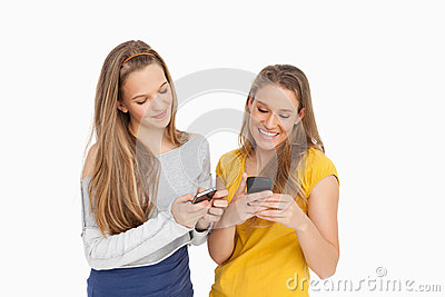 Two young women texting on their cellphones