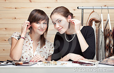Two young women trying on earrings