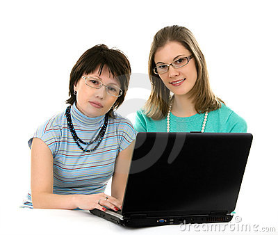 Two young women working on a laptop.