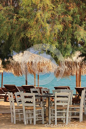 Typical greek scene at the kalyves beach with wooden chairs and table