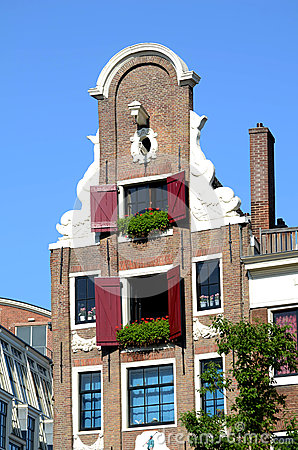 Typical house in Amsterdam with geraniums in window