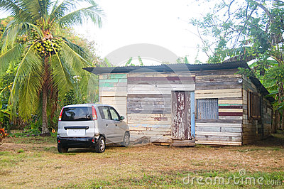 Typical native Nicaraguan wood clapboard house with taxi  jungle