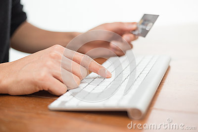 Typing on keyboard and holding credit card