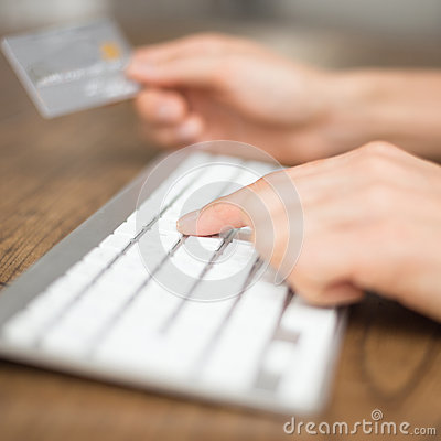 Typing on keyboard and holding credit card for onl