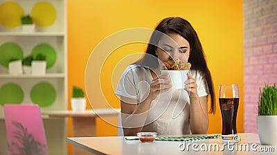 Uśmiechnięta kobieta trzyma rozporządzalnego puchar z crispy pieczonym kurczakiem, cieszy się odór zbiory