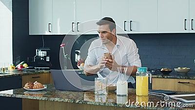 Uśmiechniętego mężczyzny dopatrywania wideo pozycja w kuchni Szczęśliwy osoby scrolling komputer zbiory