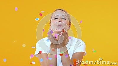 Uśmiechniętej kobiety podmuchowi confetti przeciw żółtemu tłu, partyjna rozrywka zbiory wideo