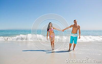 Uśmiechnięty przystojny mężczyzna trzyma jego dziewczyny rękę
