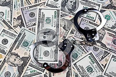 U.S. dollars bank notes and handcuffs.