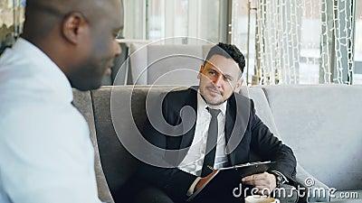 U-zakenman die baangesprek met de Afrikaanse Amerikaanse mens hebben en op zijn samenvattingstoepassing in moderne koffie letten stock videobeelden
