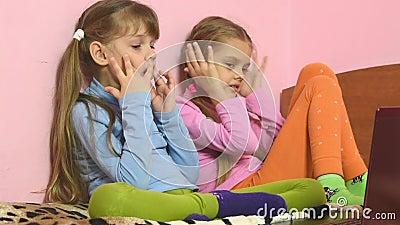 Uitdrukkingen van kinderen die aan laptop het scherm kijken stock footage