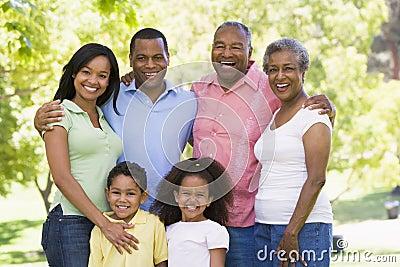 Uitgebreide familie die zich in park het glimlachen bevindt