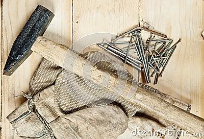 Uitstekende hamer met spijkers op houten achtergrond