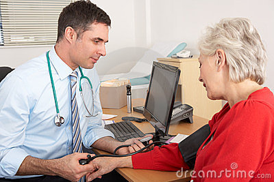 UK doctor taking senior woman s blood pressure