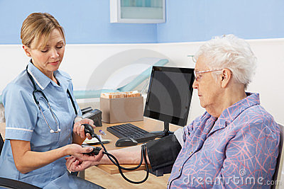 UK nurse taking senior woman s blood pressure