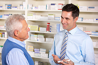 UK pharmacist serving  senior man in pharmacy