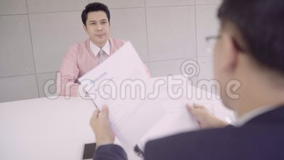 Ultrarapid - attraktiv ung asiatisk affärsman i en jobbintervju med den företags personalchefen som som läser hans CV stock video