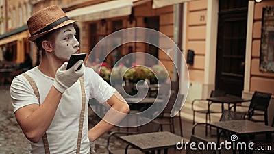 Um belo e jovem mímico com expressão facial entediada rola olhos falando ao telefone filme