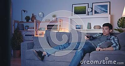 Um brunet bonito vendo TV em casa usando controle remoto relaxando no sofá video estoque