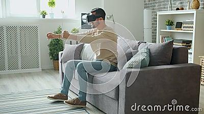 Um cara animado jogando em óculos de realidade virtual aproveitando a experiência de dirigir video estoque