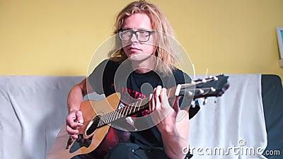 Um cara de cabelo comprido toca violão acústico video estoque