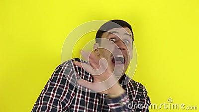 Um cara engraçado e bonito expressa seu medo e afasta as mãos do perigo Retrato sobre fundo amarelo filme
