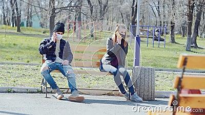 Um casal de máscaras médicas a distância e conversando ao telefone vídeos de arquivo