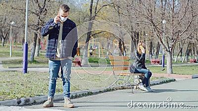 Um casal de máscaras médicas a distância e conversando ao telefone video estoque