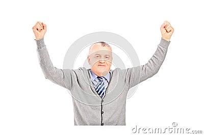 Um cavalheiro maduro assentado em uma tabela que gesticula a felicidade