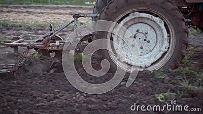 Um fazendeiro em um trator vermelho ara a terra em seu lote pequeno Trabalho para cultivar video estoque