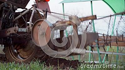 Um fazendeiro em um trator vermelho ara a terra em seu lote pequeno Trabalho para cultivar filme
