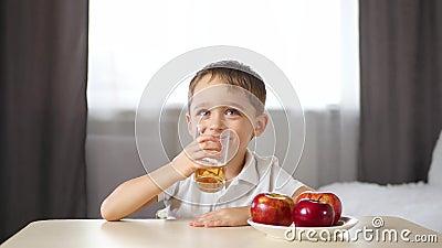 Um garotinho se senta em uma mesa e bebe suco de fruta Feliz risada infantil Conceito de alimentos saudáveis para crianças e video estoque