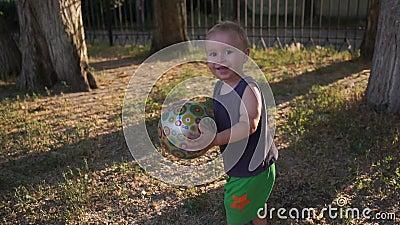Um garoto feliz com bola nas mãos sorri e ri em câmera lenta video estoque