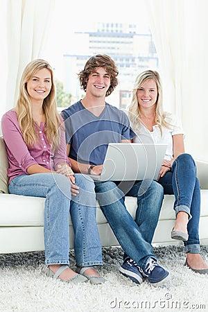 Um grupo de amigos que sentam-se junto como usam um portátil