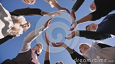 Um grupo de estudantes de pós-graduação faz um círculo com as palmas das mãos video estoque