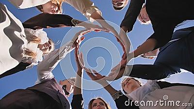 Um grupo de estudantes de pós-graduação faz um círculo com as palmas das mãos filme