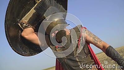 Um guerreiro romano poderoso na armadura com uma tatuagem em seu braço é coberto com um protetor, movimento lento vídeos de arquivo