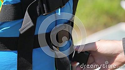 Um homem abotoa o colete salva-vidas azul filme