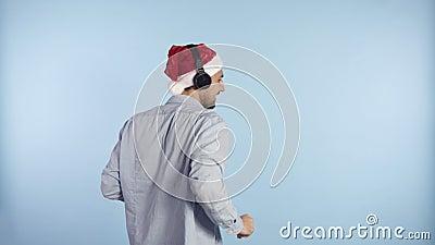 Um homem bonito, com um chapéu vermelho de Natal, a ter auscultadores, a ouvir a sua música favorita e a dançar em liberdade video estoque
