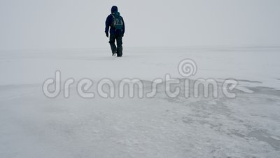Um homem caminha numa superfície congelada de um lago video estoque