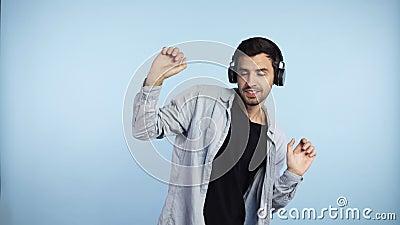Um homem caucasiano feliz colocando seus fones de ouvido pretos e começando a dançar em ritmo de melodia, fecha os olhos ouve alt vídeos de arquivo