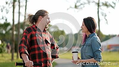 Um homem de meia idade atrativo relaxado com cabelo cinzento longo em um pontapé-'trotinette' e uma jovem mulher com cabelo tingi filme