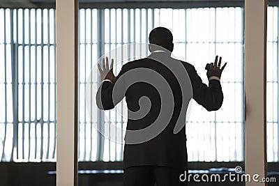 Um homem de negócio que olha para fora através de uma parede de vidro dentro