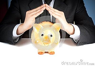 Um homem de negócios faz com sua mão uma casa atrás de um mealheiro, conceito para o negócio e salvar o dinheiro