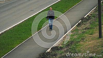 Um homem está andando ao longo do passeio na cidade filme