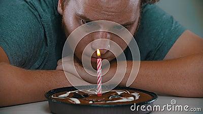 Um homem está olhando para uma vela no bolo filme