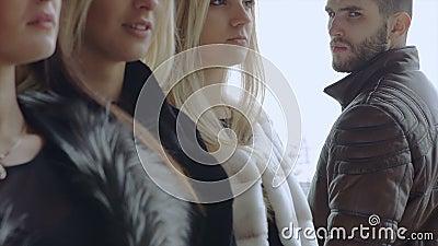 Um homem farpado novo olha três mulheres dentro video estoque