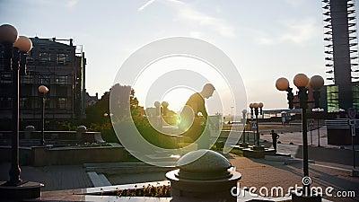 Um homem que corre no suporte e no salto na saliência - por do sol filme