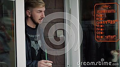 Um homem sai de uma cafetaria video estoque