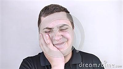 Um homem se agarra à sua bochecha e se inclina na dor do dente O conceito de problemas dentários, cáries, cárie dentária, fluxo F filme